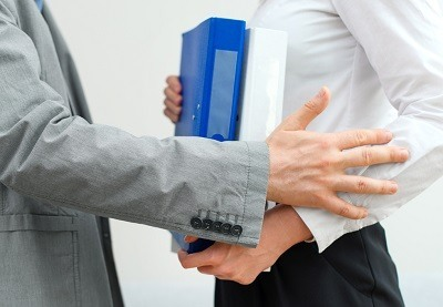 Man grabbing arm of woman carrying binders