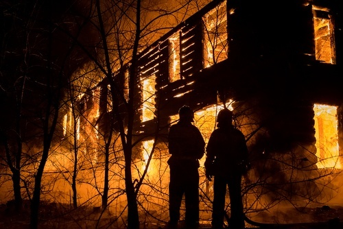 Two fireman standing in front of a burning house