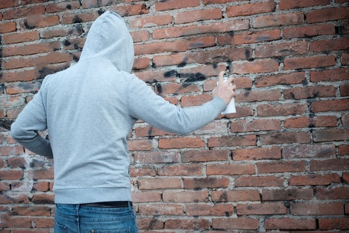 Young man in hoodie spray painting graffiti onto a brick wall