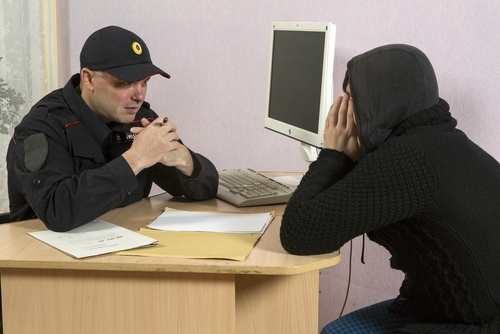 Police officer questioning a young man in a hoodie at a desk