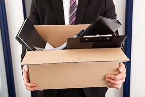 Businessman carrying belongings in box