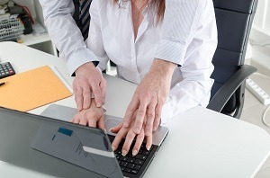 Man putting hands on female coworker's hands at computer