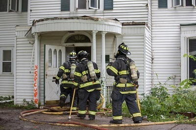 firefighters entering damaged house