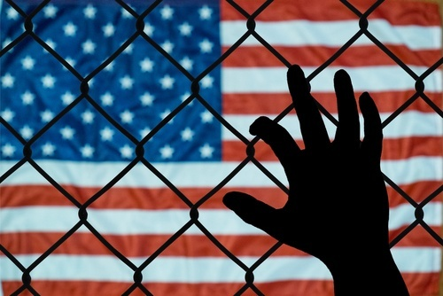 hand against chain-link fence with American flag on the other side