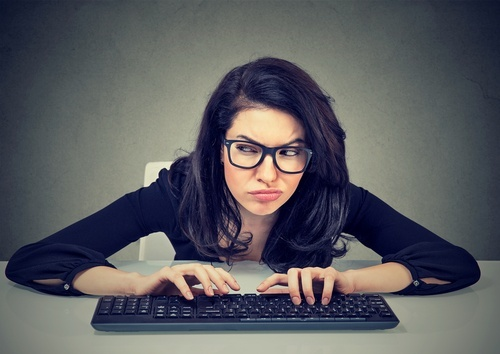 Woman in glasses squinting and leaning forward over a computer keyboard