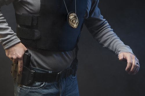 A police officer pulling his gun out of his holster