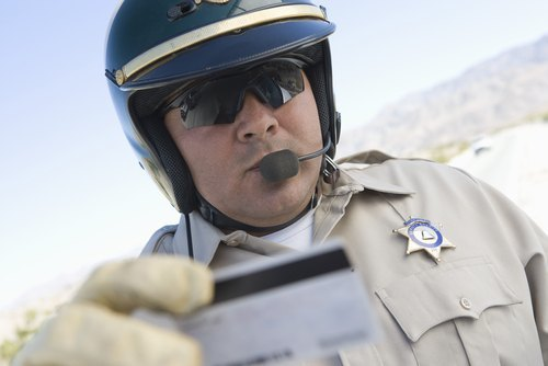Middle aged traffic cop checking driving license