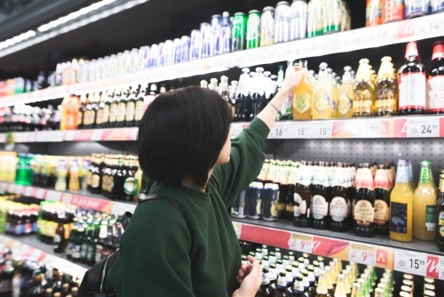 Young girl reaching for an alcoholic beverage at a convenience store