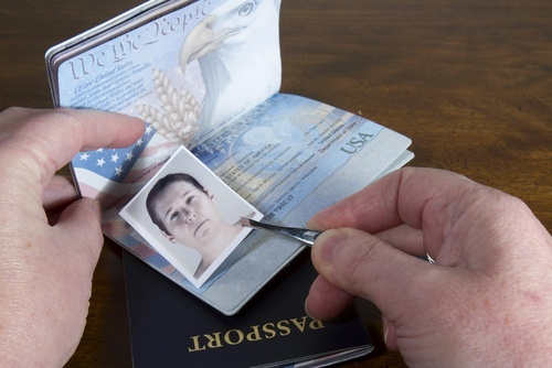 A man is placing the picture of an older woman on another person's ID