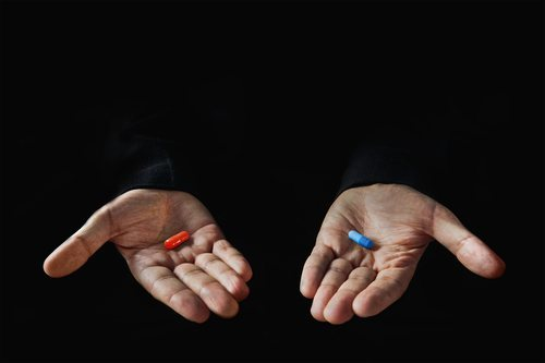 Two hands, one holding a blue pill, the other a red pill