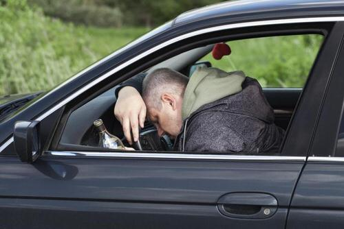 man slouched over the wheel of his car with an alcoholic beverage in his hand