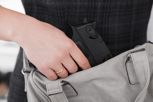woman carrying gun in bag