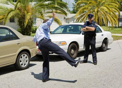 man doing a balancing act in front of a cop