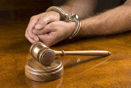 man has hands cuffed in front of judge's gavel