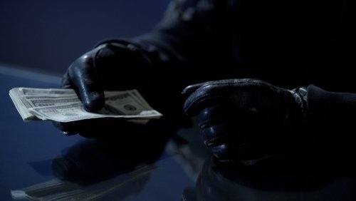 person wearing gloves holding money