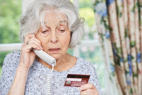 elderly lady giving credit card information over phone