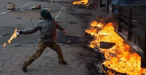 man throwing molotov cocktail