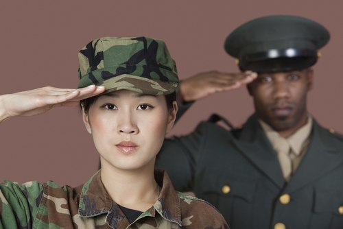 Young Asian female U.S. Marine Corps soldier and African American male officer saluting