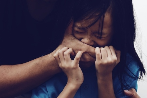 Man's hands covering mouth of scared young Asian girl