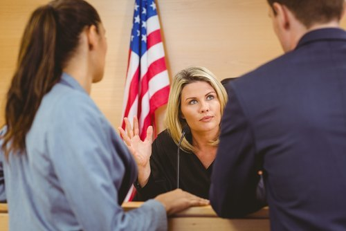 One male and one female lawyer talking to a female judge with an American flag in the background