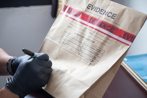 gloved hand signing evidence bag