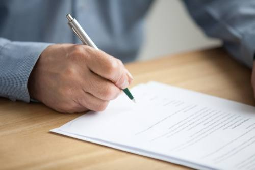 adult male signing a document
