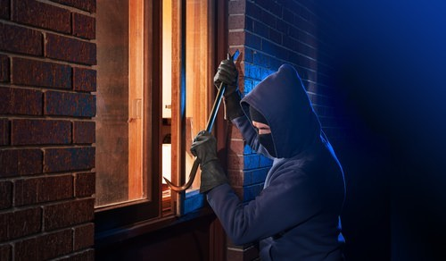 burglar using crowbar to enter through a window