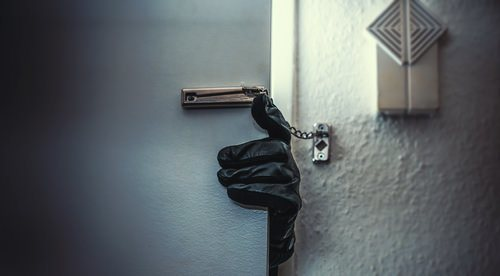 gloved hand reaching around door to break into a home as an example of Penal Code 601 PC aggravated felony trespass