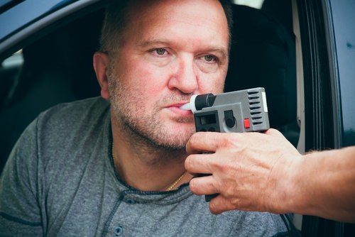 man being given breathalyzer test