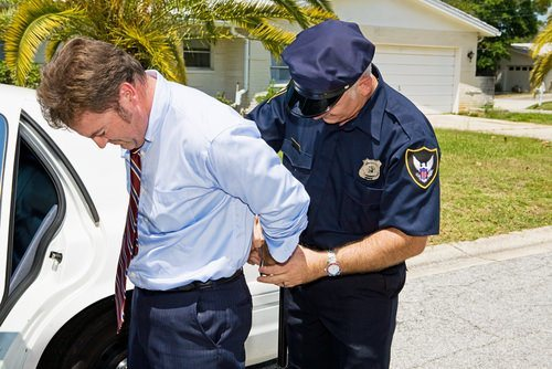 man being placed into handcuffs by police officer