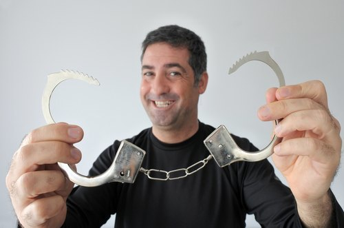 smiling 40-year old man holding up an open pair of handcuffs