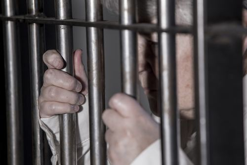 elderly woman holding onto the bars of her prison cell