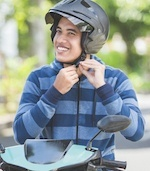 Man buckling helmet while mounting motorcycle