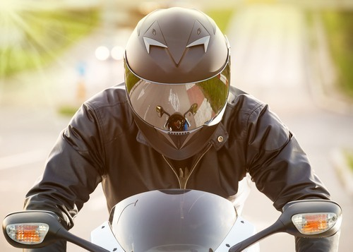 Man on motorcycle with helmet.
