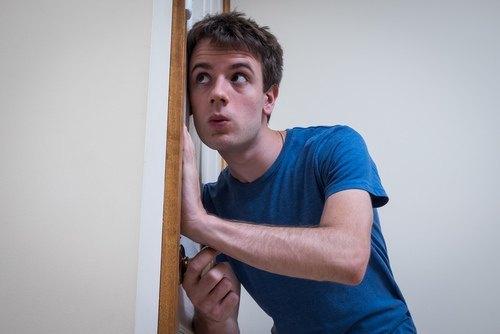 man eavesdropping through door