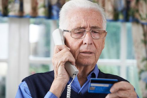 senior male giving credit card information over phone