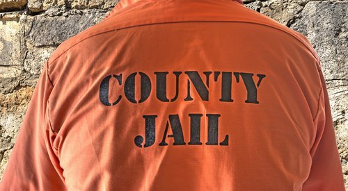 person wearing orange county jail shirt