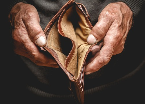 elderly man opening his empty wallet
