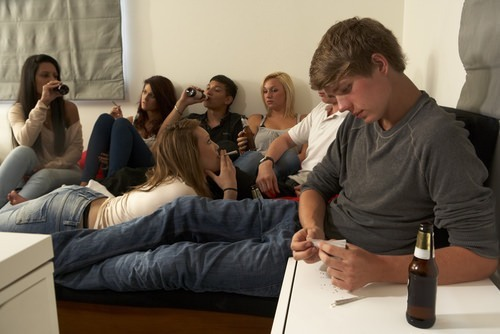 teens drinking alcohol and smoking cigarettes in a room