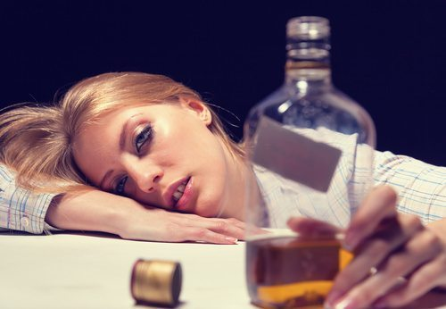 teen passed out on table with a bottle of liquor in front of her