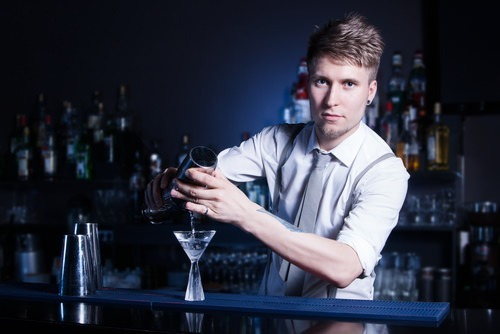 bartender pouring a drink into martini glass