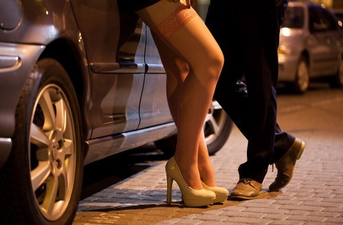 prostitute and john chat in front of a car at night