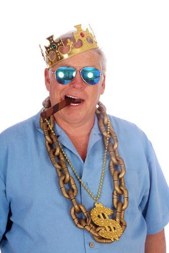 man with cigar in mouth and gold chains around neck