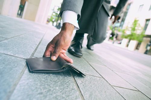 man picking up wallet from floor