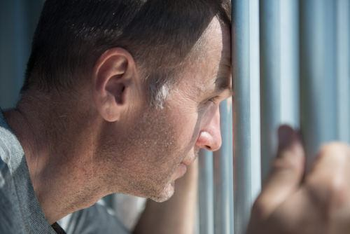 male inmate looking out of a jail cell - a Vehicle Code 14601.4 VC violation can be punished by up to one year in county jail.