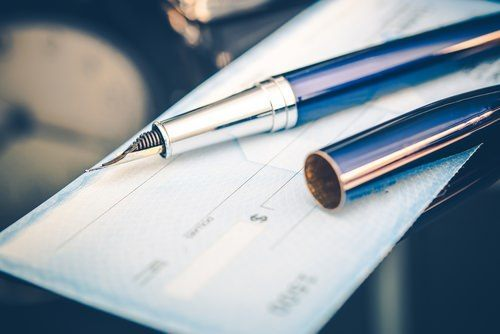 fountain pen laying atop a personal check