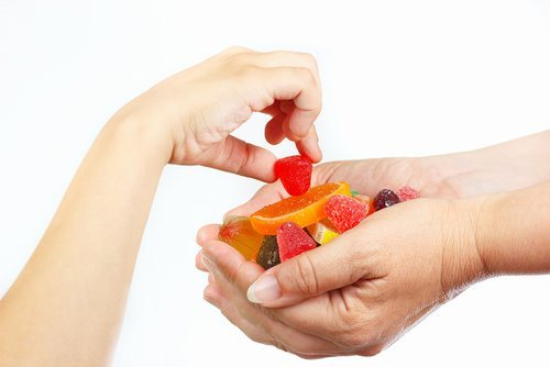 child reaching for candy from adult's hands