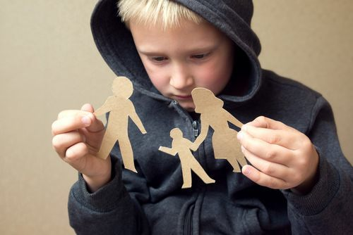 child holding up paper cutout of family