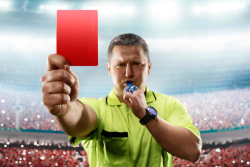 referee pulling out a red card in a soccer match