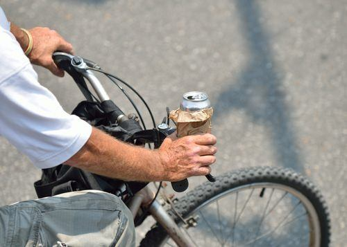 man on bicycle holding a can of beer as an example of cycling under the influence per Vehicle Code 21200.5 VC